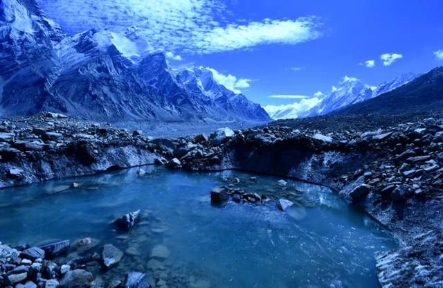 A small but every increasing number of glacial lakes swell with meltwater. To the left are the 3 Bhagirathi Sisters' Peaks.