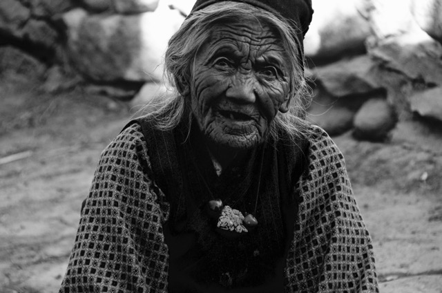 Day 8 of Tributes: The Incense Maker. In the walled city of Lo Mantang, Nepal this woman could be found in any number of places sitting on a folded rug pounding herbs with a stone into the basics of incense. Mornings she pounded, afternoons she pounded...as though her task would never end. Sitting, oblivious to the cold, she would spread out the intact herbs, place some into a centuries' old recess in the stone and ground the elements with a worn stone. Smells would waft up and be passed around by the winds, so that we would know that she was close before we would see her. Though incense can be found in any shop, it was as though she was proving that the old ways were the only ways. Her hands were stained, powerful, and pieces of beauty.